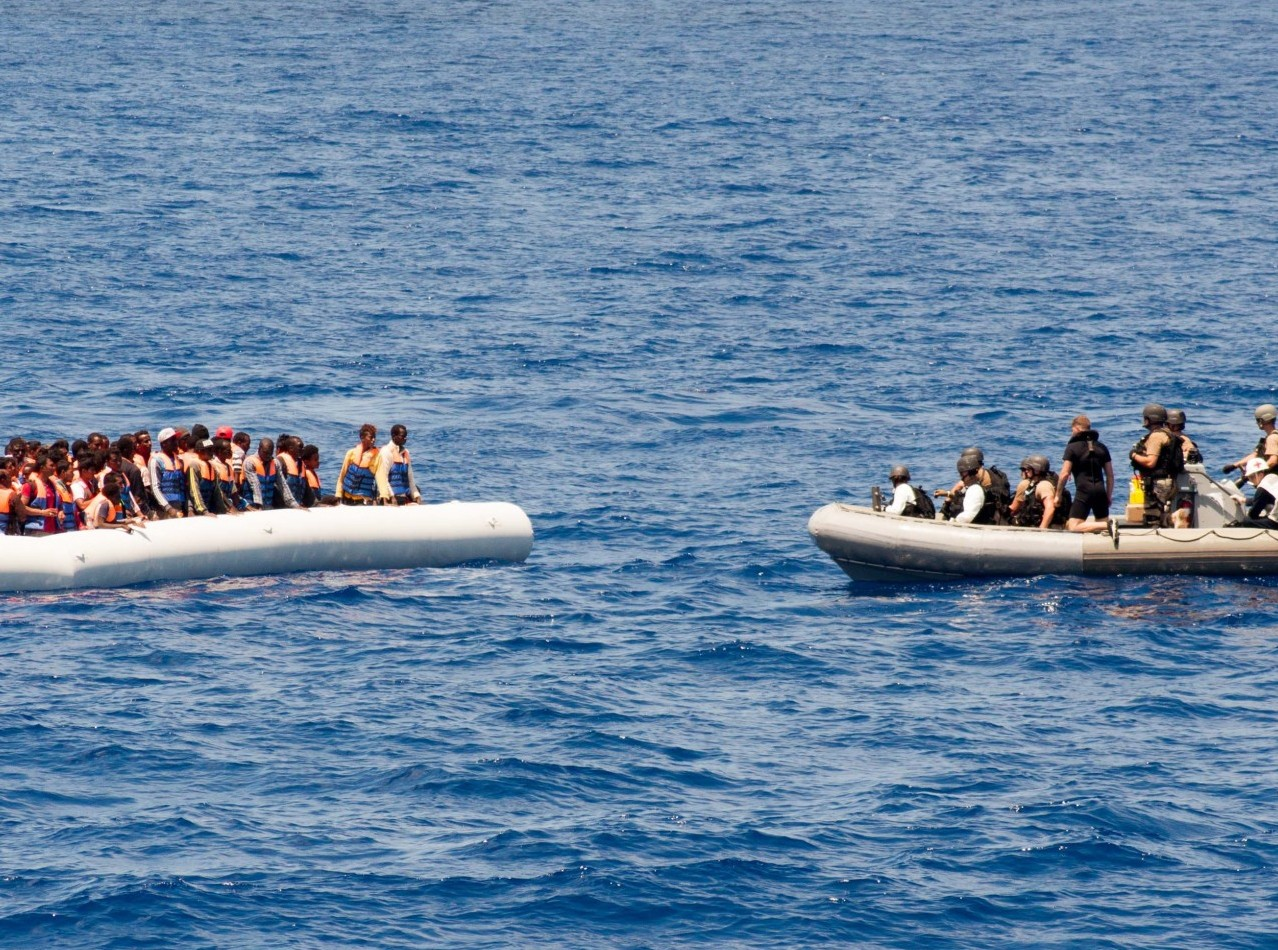 Sailors approach a small craft full of migrants while on patrol in the Mediterranean Sea. Source: Commander, U.S. Naval Forces Europe, Flickr, Public Domain